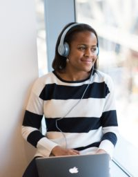 Woman wearing headphones looking out a window