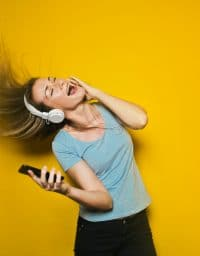 woman waving her hair in the air while listening to music through headphones