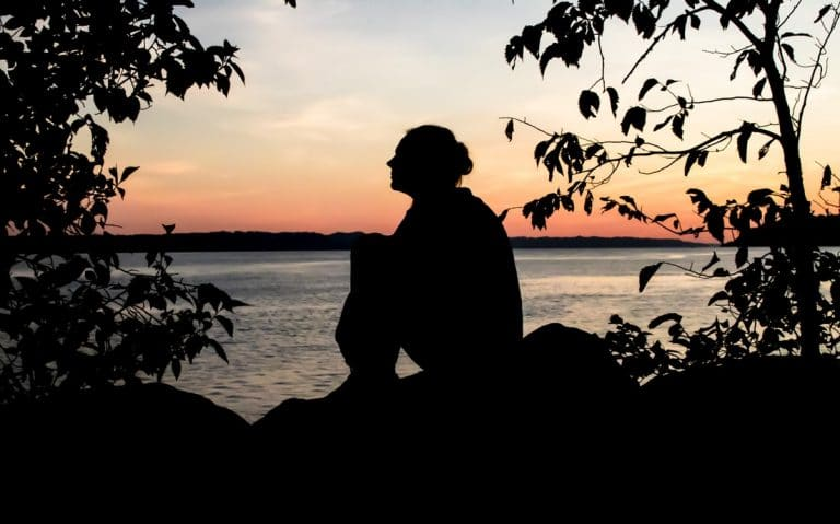 Woman sits outside in sunset.