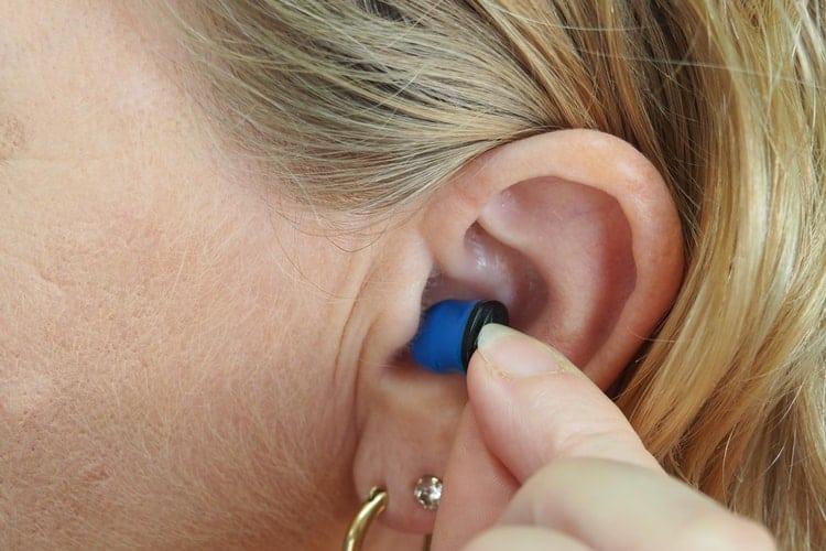 Woman inserts ear plugs.